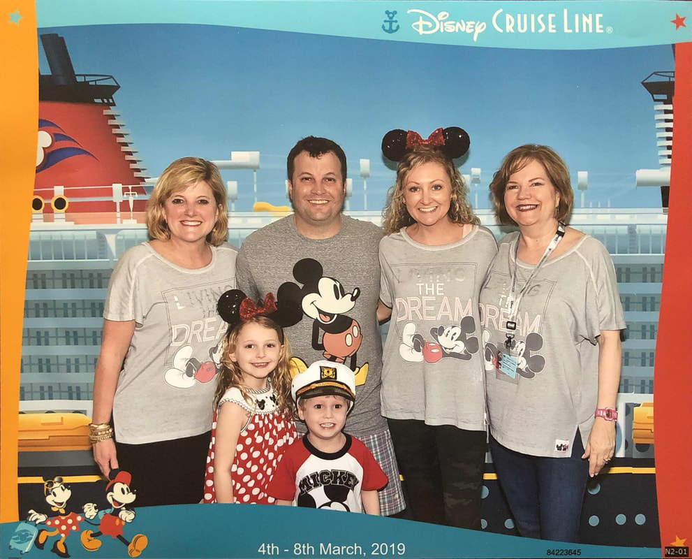 Group picture of 4 adults,  2 kids in Disney shirts right before boarding Disney Cruise