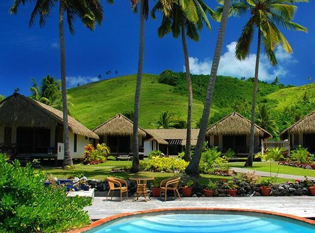 Pool beside beautiful thatched bungalows